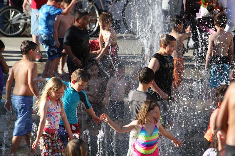 by: HILLSBORO TRIBUNE PHOTOS BY DOUG BURKHARDT - Hillsboros Tuesday Market is a cool place to be! On July 1, youngsters enjoyed splashing in the fountain on a 90-degree day, while other daring kids lined up to take a wild spin in a twirling anti-gravity device.