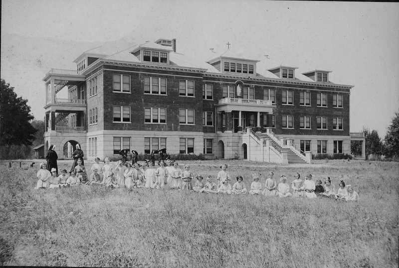by: SUBMITTED PHOTO - The Christie Building, here shown early in the 20th century with orphans and nuns, is still being used today on the campus of Marylhurst University.  But its future as a historic landmark is in question.