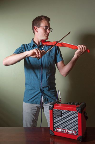 by: TRIBUNE PHOTOS: JONATHAN HOUSE - David Perry of OpenFab PDX plays a violin he created digitally and produced on a 3D printer. The violins honeycombed interior can easily be changed to a different, more resonant pattern.