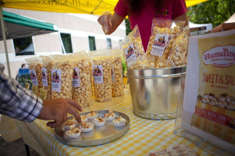by: TRIBUNE PHOTO: ADAM WICKHAM - An attendee grabs a sample of Humdinger Kettle Corn.