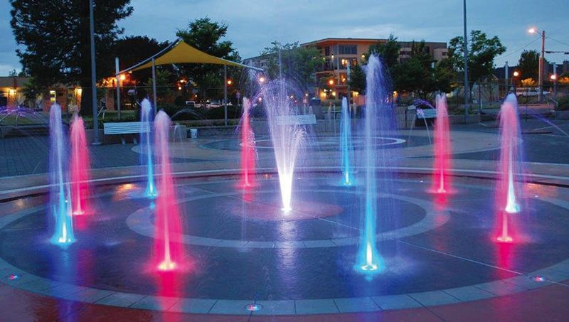 by: CONTRIBUTED PHOTO: CITY OF GRESHAM - The city opened the new Childrens Fountain in the Arts Plaza on July 4 where children can play in two fountains - one for big kids and one for toddlers  - that are powered by 43 computer controlled jets and lit by a display of 20 multi-colored lights at night.