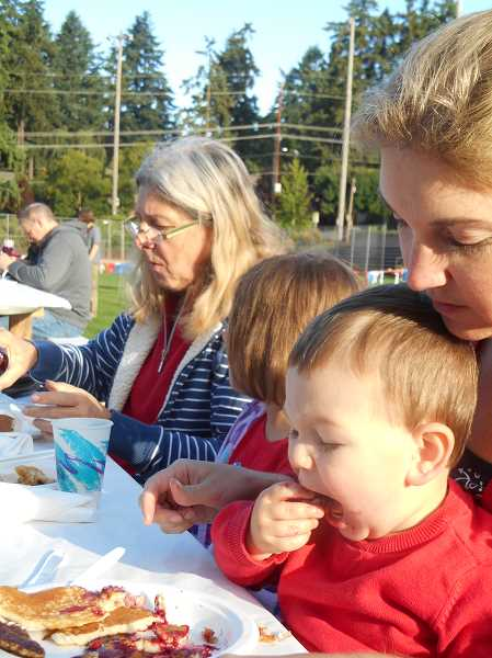 by: REVIEW PHOTO: GARY M. STEIN - Reed Jorling doesnt need much encouragement from mom Brandy at the Lions Club Fourth of July pancake breakfast in Lake Oswego.