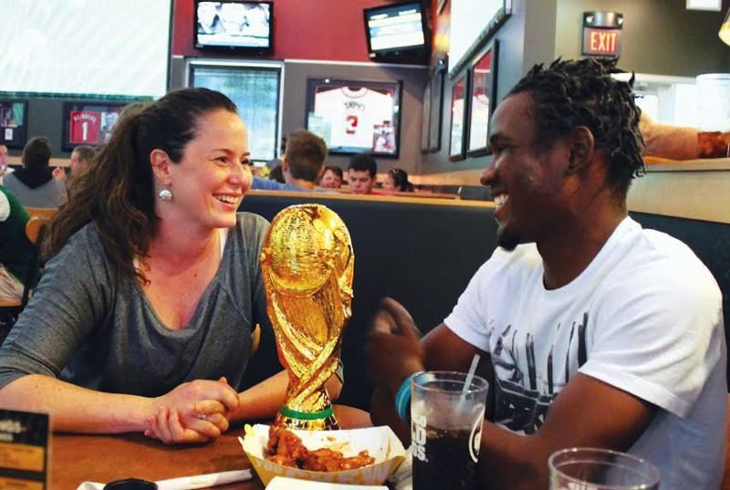 by: OUTLOOK PHOTO: LISA K. ANDERSON - Jeanie Hodge and Marc-Ernst Laguerre met in Haiti several years ago during a medical trip. Now the friends are reunited, with Laguerre attending Mt. Hood Community College. They've been watching World Cup games together at East County spots.