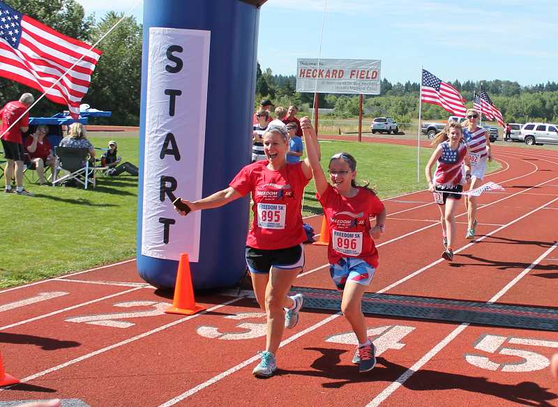 by: JIM BESEDA/MOLALLA PIONEER - Milwaukie's Wendi Arant (895) and 10-year0old daughter Rachel Arant cross the finish line in 44:06 at Friday's Freedom 5K run in Molalla.