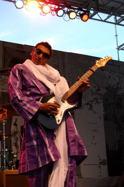 by: TRIBUNE PHOTO: KEVIN ANSPACH - Guitarist Omara 'Bombino' Moctar cut loose in his colorful clothing and his bluesy set during Thursday's Safeway Waterfront Blues Festival.