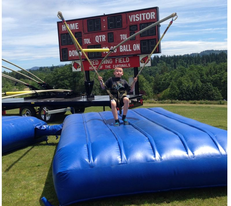 by: OUTLOOK PHOTO: LAURA KNUDSON - Maddox Leith-Ross strapped into a harness to try to monkey bounce at the Corbett Fun Fest. The eight-year-old did a series of back flips and was anxious to try again, even though the experience made him dizzy.
