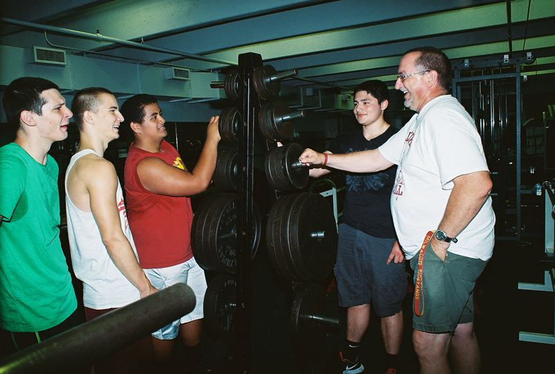 by: JOHN DENNY - Milwaukie football coach Jon Wolf wasted little time in putting some of his football players to work rearranging the high school weight room for his movement dynamics program, which features both weight lifting and agility training. Pictured with the new Mustang head coach are (from left) Ivan Smith, River Meyer, Tui Tuitele and Patricio Hernandez. Wolf encourages any Milwaukie High School athlete, regardless of their sport, to take advantage of the movement dynamics program. Sessions run from 9 to 11 a.m. and from 4 to 6 p.m. Mondays through Thursdays through the summer.