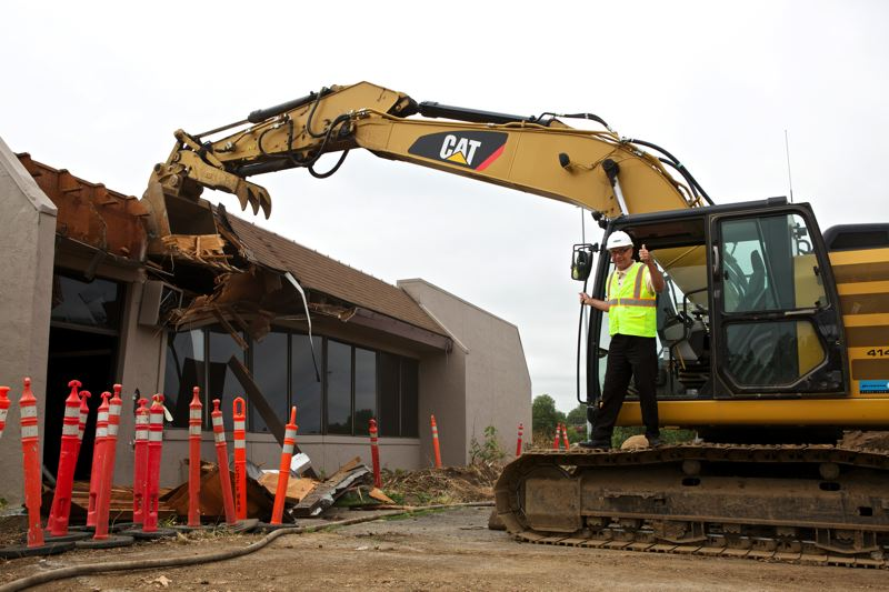 by: TIMES PHOTO: JAIME VALDEZ - Tualatin Mayor Lou Ogden took a turn using a track hoe to help level Jiggles, which stood at Tualatin's entryway for 30 years.
