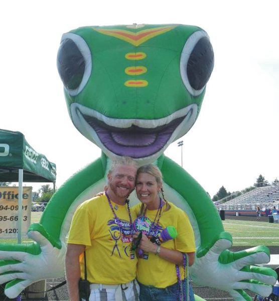 by: SUBMITTED PHOTO - Michael and Jackie Henderson are pictured above within the open arms of the mascot for Geico, the Milwaukie Relay for Life sponsor in 2012.
