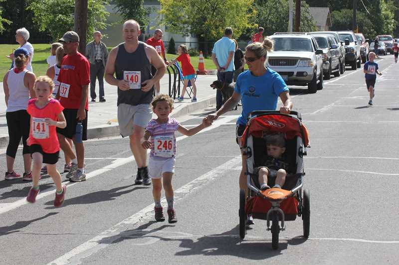 by: JEFF WILSON/THE PIONEER - Bella Dubisar (246) runs in the Two-Mile Fun Run Friday with her mother Lisa and brother Eliot while Jestina Sullivan (141) and her father Shaun are along for the jog.