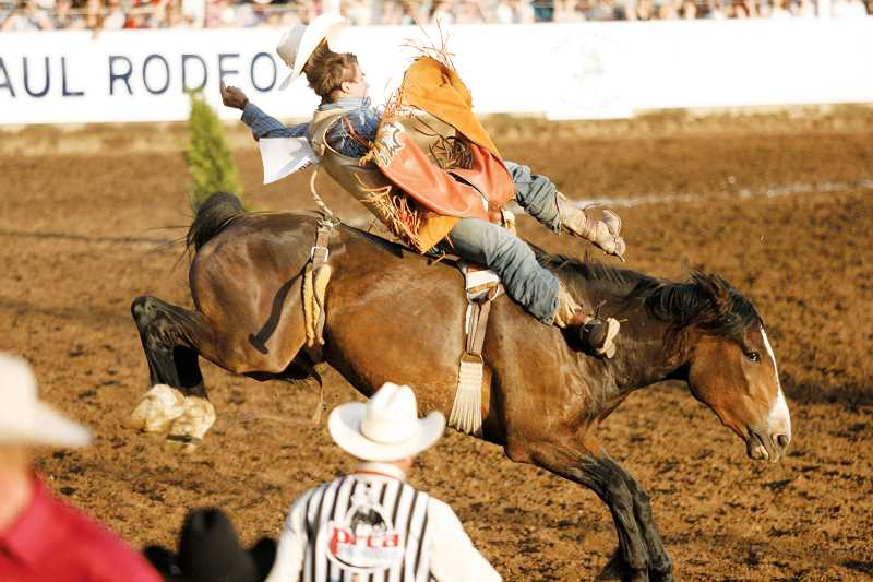 by: PHIL HAWKINS - Tyler Waltz of Martin, Tennessee, holds onto I Spy Major of Big Stone in the first go of the bareback riding competition Wednesday at the 79th annual St. Paul Rodeo.