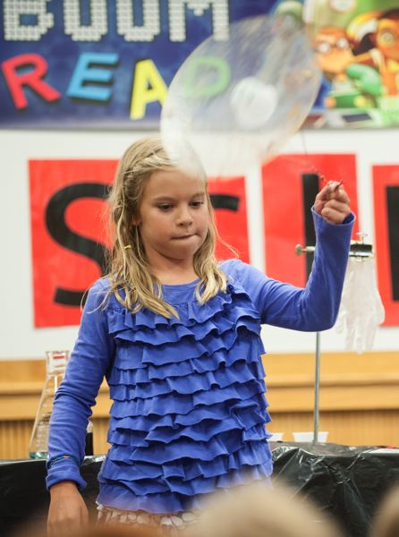by: SPOKESMAN PHOTO: JOSH KULLA - Wilsonville girl Kami Gore takes part July 3 in an experiment in centrifugal force as part of the Mad Science summer show at the Wilsonville Library.