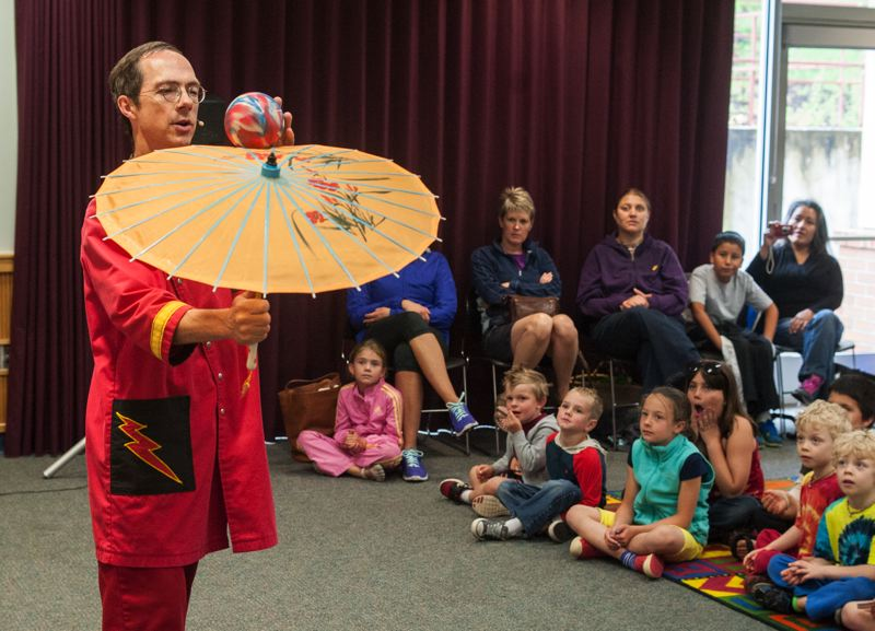 by: SPOKESMAN PHOTO: JOSH KULLA - Comedic Juggler Rhys Thomas packed the Wilsonville Library June 26, with three sold out shows filling the Oak Room with children.