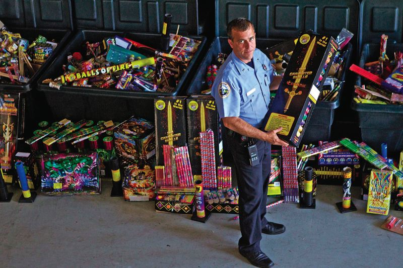 by: TRIBUNE PHOTO: KEVIN HARDEN - Each year, thousands of illegal fireworks are seized by local law enforcement. Here, Portland Fire & Rescue Public Education Officer Michael Silva holds one of the 45,000 illegal fireworks that he collected last year. The fireworks were sent to an undisclosed location in November to be destroyed.