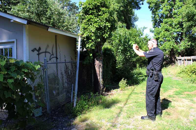 by: NEWS-TIMES PHOTO: KATE STRINGER - Corporal Mark Trost takes photos of graffiti in an alleyway between houses during a patrol July 1. The Washington County Sheriffs Office began running Cornelius police services this month.
