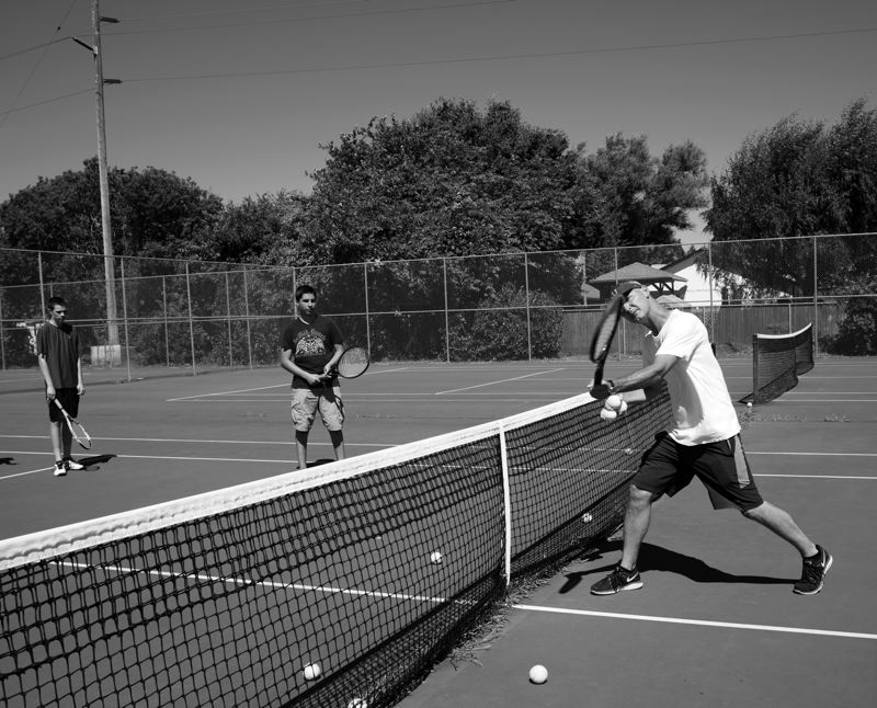 Forest Grove assistant tennis coach T.J. Buehler gives instruction to a pair of players at the Tennis in the Grove youth program on Monday. The series of tennis clinics runs each week until the end of August.