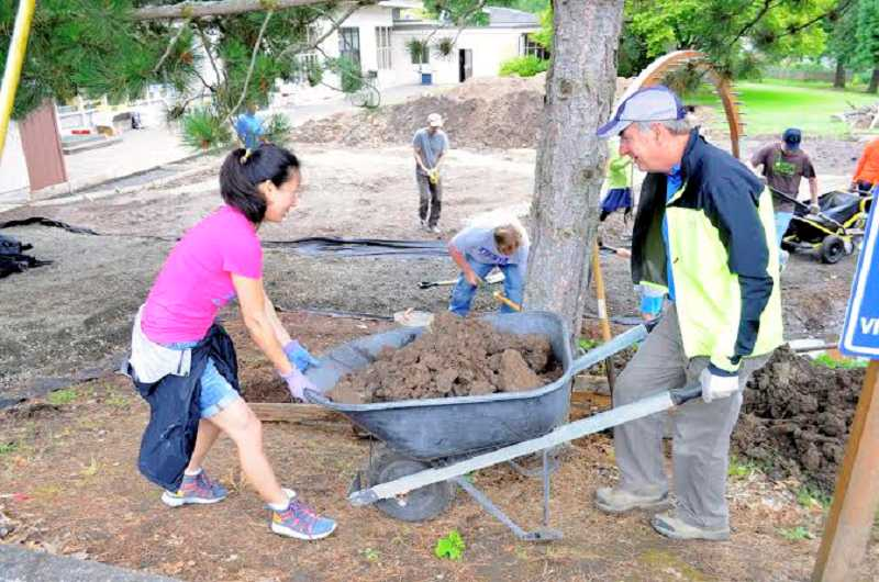 by: CONTRIBUTED PHOTO - Volunteers help make progress on the the nature playscape project at Cedar Hills Kindergarten and Preschool on Southwest Park Way on June 28.