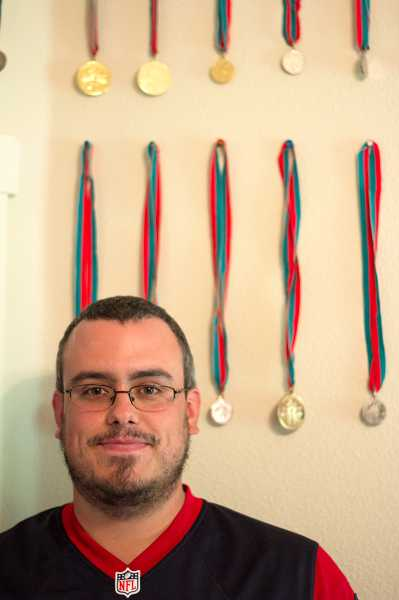 by: TIMES PHOTO: LACEY JACOBY - Aloha resident Brandon Wynne shows off some of the many awards he's accumulated over the years while participating in softball and baseball competitions through Special Olympics Oregon.