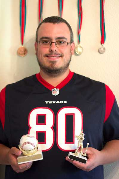 by: TIMES PHOTO: LACEY JACOBY - Aloha resident Brandon Wynne shows off some of the many awards hes accumulated over the years while participating in softball and baseball competitions through Special Olympics Oregon.
