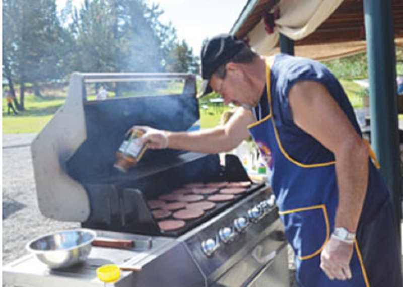 by: STEPHANIE RODERICK - Bob Kistrba, of Crooked River Ranch, cooks buffalo burgers during the Lions Club Buffalo Feed at the Ranch on July 5, shortly after the Ranch's Independence Day parade.