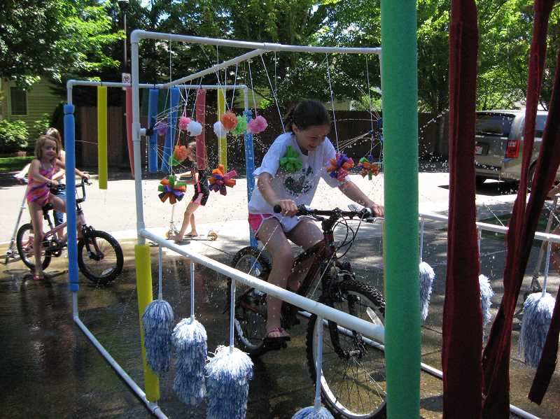 Photo Credit: GAZETTE PHOTO: RAY PITZ - Chloe Hales, followed by her sister, Kate, takes a ride through a handmade bike wash their father, Colin, helped construct.