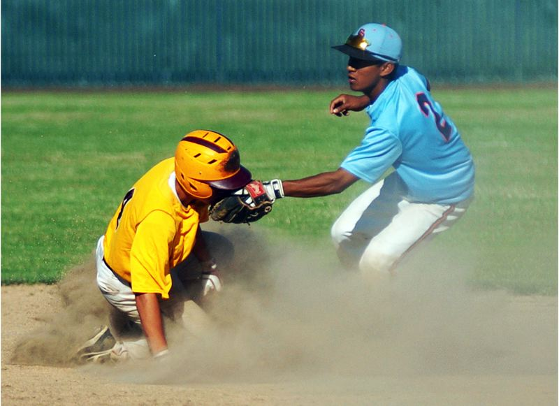 by: DAN BROOD - CLOUD OF DUST -- Suburban Door second baseman Bryce Haskin (right) puts a tag on a Forest Grove runner on a stolen base attempt.