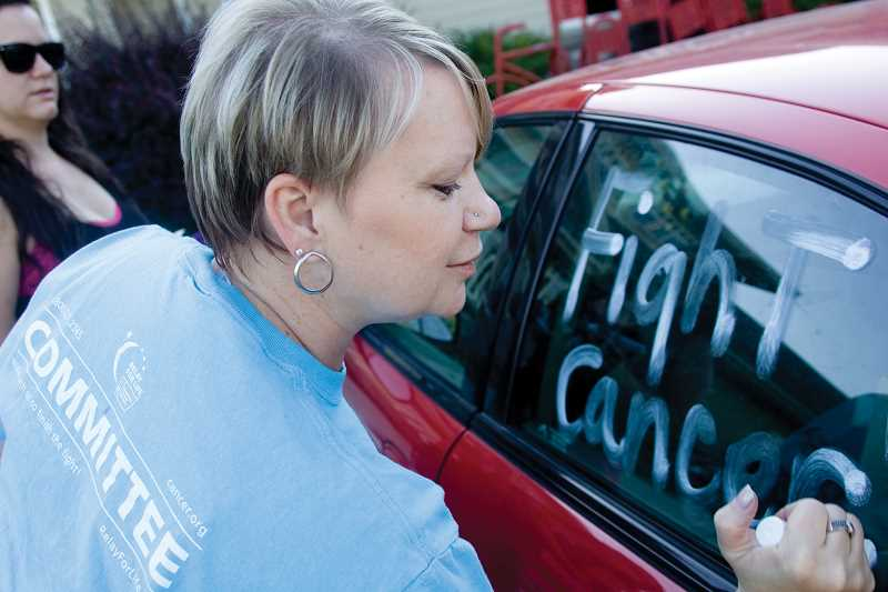 by: KEVIN SPERL - Rita Amodeo decorates the windows of a car for the upcoming Relay for Life event in Prineville.