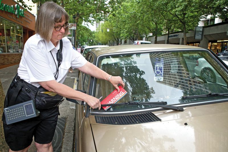 by: TRIBUNE PHOTO: JAIME VALDEZ - Parking code enforcement officer Becky Rhodes places a warning on a car parked downtown with a disabled driver permit. Under city rules that began July 1, disabled drivers must pay for metered spaces.