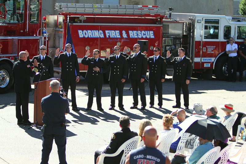 by: PHOTO COURTESY: BRANDON PAXTON - Clackamas Fire District No. 1 chief Fred Charlton swears in Boring Fire District firefighters during the July 1 ceremony.