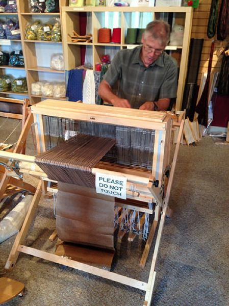 by: PHOTO BY MICHELE BERNSTEIN - Thomas Betts, co-owner of Hood River's Cascade Alpacas of Oregon, demonstrates the ins and outs of weaving with alpaca wool.