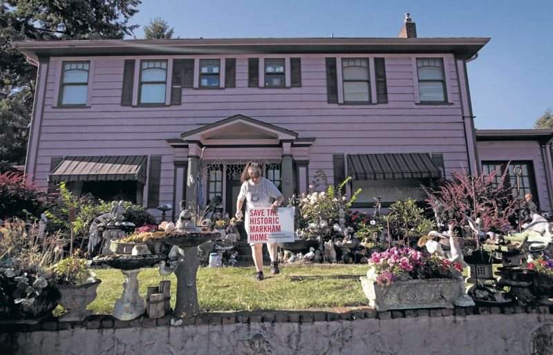 by: TRIBUNE PHOTO: JONATHAN HOUSE - Longtime Northeast Glisan Street resident Loretta Forman plants a sign showing her support for saving a historic home in her neighborhood.