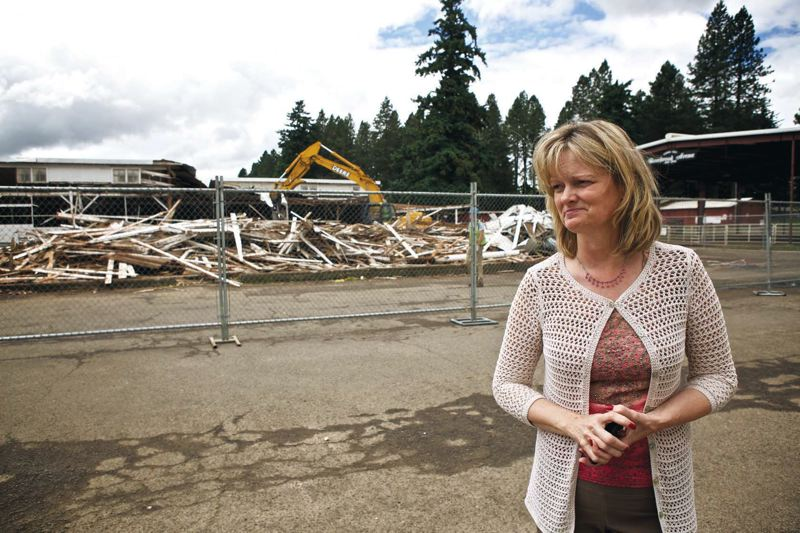 by: TRIBUNE PHOTO: JAIME VALDEZ - Laurie Bothwell, executive director of the Clackamas County Fair, stands as the livestock barn is demolished.