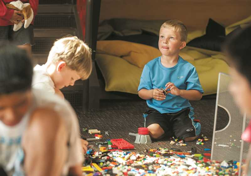 by: SPOKESMAN PHOTO: JOSH KULLA - Chase Buchanan, 5, builds with Legos last Wednesday as part of Lowrie Primary School's summer library program for local kids.