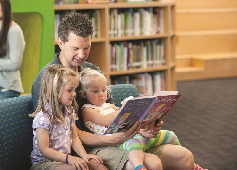 by: SPOKESMAN PHOTO: JOSH KULLA - Lowrie Primary School PTA President Travis Tadema reads last week with his two daughters, Juliet and Eliana, at Lowrie's summer library program.