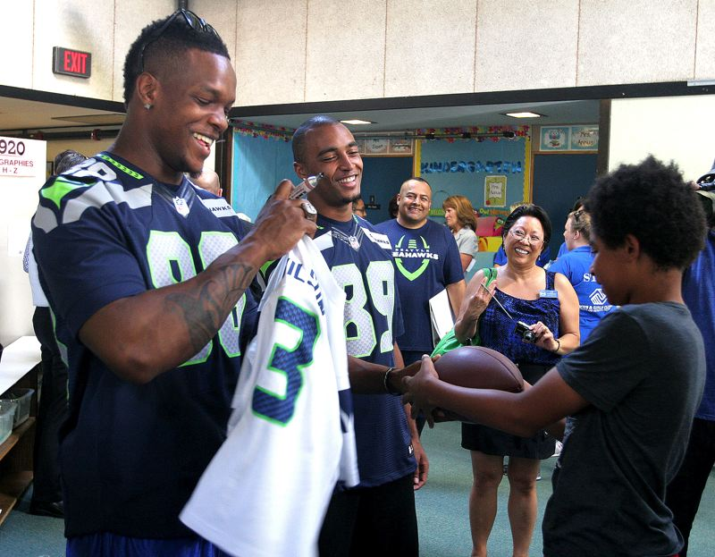by: OUTLOOK PHOTO: JIM CLARK - Phil Bates, left, and Doug Baldwin, right, wide receivers for the Seattle Seahawks, sign jerseys for young fans as Gresham city councilor Lori Stegmann looks on.