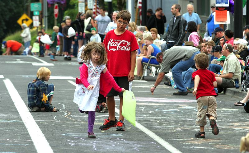 by: FILE PHOTO - Children play amidst the chalk drawings they made at last years Troutdale SummerFest, which takes place again this Saturday.
