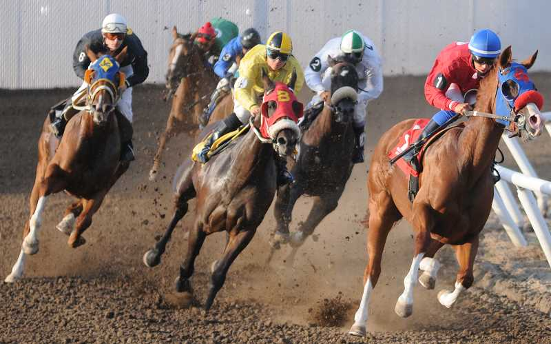 by: LON AUSTIN/CENTRAL OREGONIAN - Horses come off the corner during the first race Saturday at the Crooked River Roundup Race Meet. Sing And Swing, ridden by Jose Guerrero in white, came from behind to win the race. Yuma Landing, ridden by Jake Samuels in red, came in second in the race.