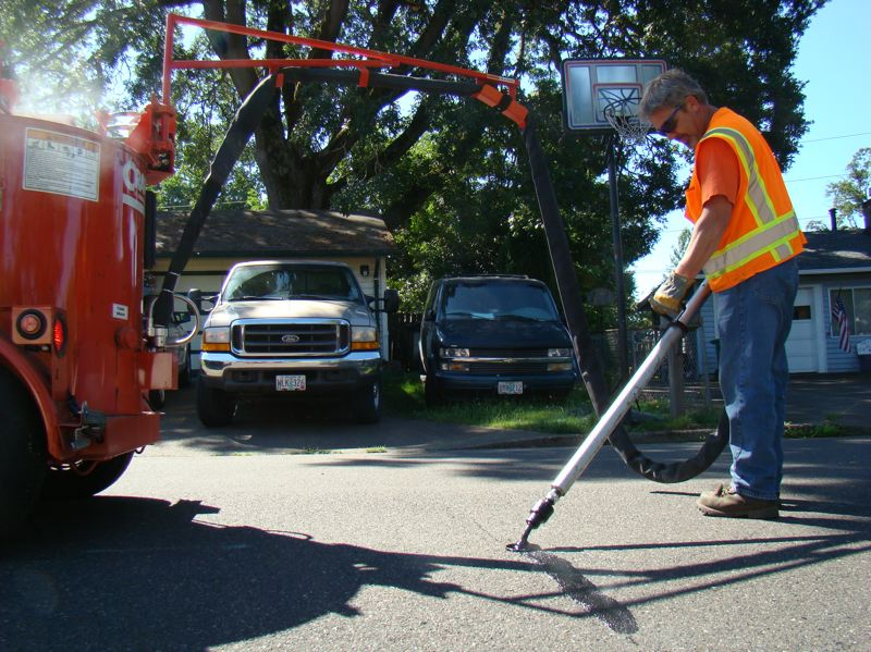by: PHOTO COURTESY: CITY OF MILWAUKIE  - Jim Bunting of Milwaukie's Streets Department works in various neighborhoods this month to seal cracks.