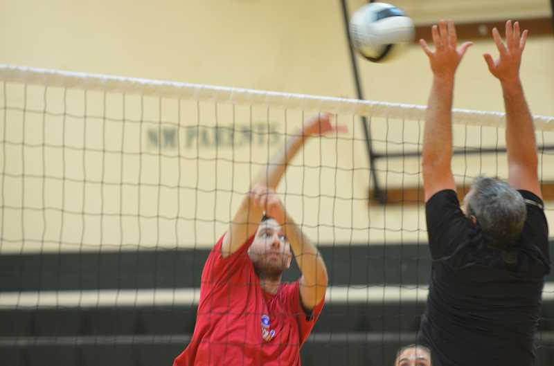by: COREY BUCHANAN - Doyle Tracy (right) blocks a shot from an opponent during Saturday's volleyball tournament at North Marion, which raised money for team uniforms.