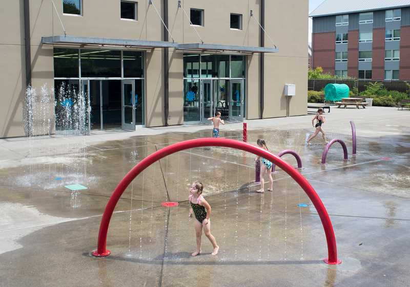by: NEWS-TIMES PHOTO: CHASE ALLGOOD - Children frolicked in the spray park at the Forest Grove Aquatic Center Friday as temperatures began to rise. Despite a brief period of rain Sunday, this weeks weather is expected to stay in the 90- to 100-degree range.