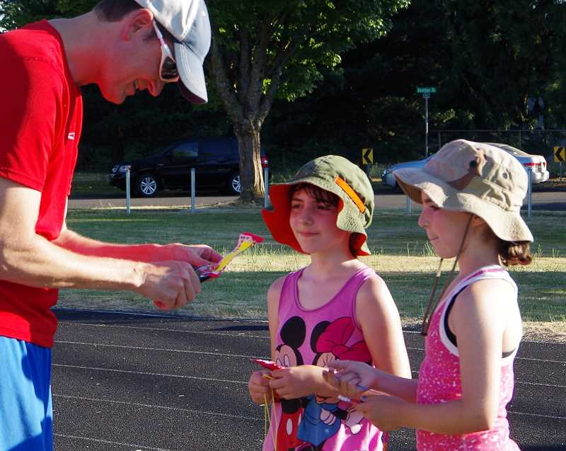 Cousins Camryn Pilatti and Rebecca Frawley, both 11, get their lap cards punched by T.J. Gray of Mountain View Medical Center, which gave each walker a reusable band with a pedometer and chapstick every 11.5 laps.