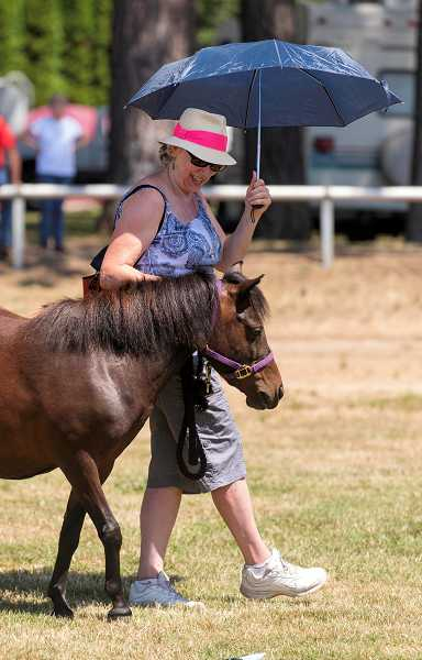 Parasol in hand, Donna Sullivan, of Troutdale, leads Lightning, the pony her granddaughter, Alison Hartman, will show in the 4-H Horse Fair at the Clackamas County Event Center.
