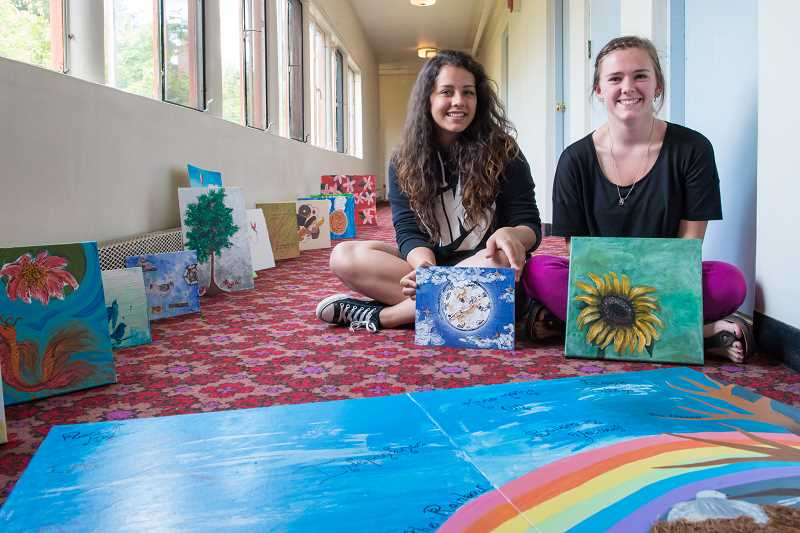 by: STAFF PHOTOS: CAITLIN TOMPKINS - WLHS students Kathy Zumbado, left, and Shalie Reay created a large art piece together of a tree and rainbow as a gift to the residents at the LifeChange Center for Women and their Children. Other art students created more art which was given to the center.