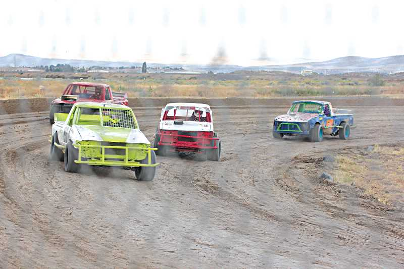 by: JEFF WILSON/THE PIONEER - Kim Coen, in the green and white mini truck, races through the fourth turn during early runs Saturday night at the Madras Speedway. The track hosted its 11th Annual Race For the Kids in front of a packed house.