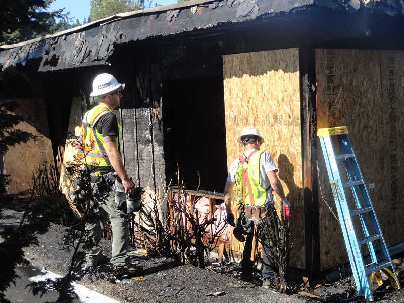 by: TIDINGS PHOTO - Workers board up one of the units damaged in the fire.