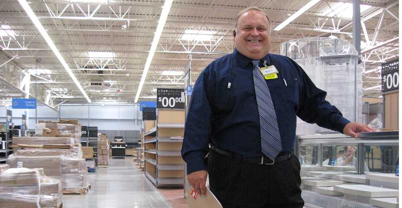 Photo Credit: GAZETTE PHOTO: RAY PITZ - Sherwood Walmart Supercenter Manager Scot Gavic stands next to a jewelry aisle that will soon be filled with merchandise. The store will open bright and early Aug. 13.