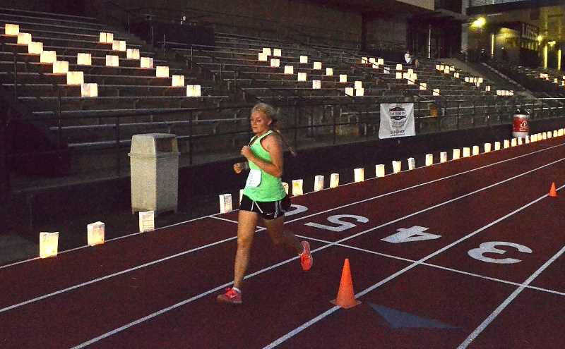 by: REVIEW PHOTO: VERN UYETAKE - Amy Moring, a junior at Lake Oswego High School, runs past the grandstands where luminaria spell out Hope and Cure.