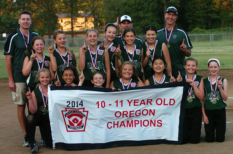 by: DAN BROOD - THE CHAMPS -- Players and coaches for the Tigard Little League ages 10-11 all-star softball team poses with the state championship banner following their title-game victory over Centennial.