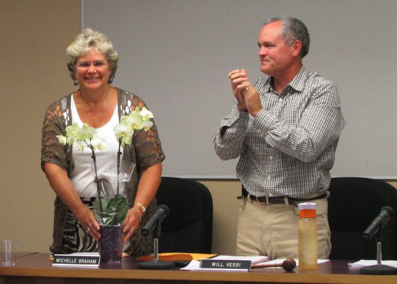 by: MARK MILLER - Michelle Graham (left) beams after receiving flowers from Superintendent Stephen Jupe of the Scappoose School District, upon relinquishing chairmanship of the school board to Will Kessi (right).