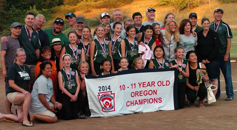 by: DAN BROOD - Tigard Little League softball players, coaches, family and friends gather with the state championship banner.